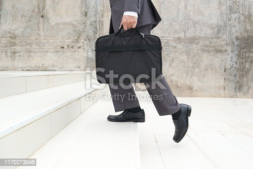 684803840istockphoto Business man step up stair.Lower part of Man in business shoes walking up stair,People lifestyle successful and competition concept 1170273045