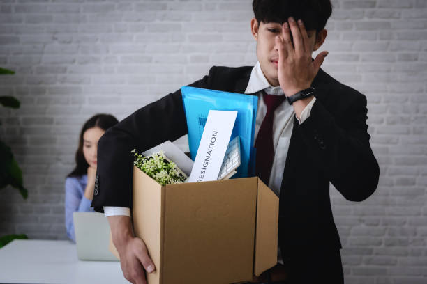 Business man stressed after resignation or be fired  from business company with holding cardboard box packing her belonging and boss on background. stock photo