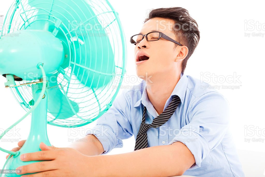 business man  suffering a hot  summer heat with fans stock photo