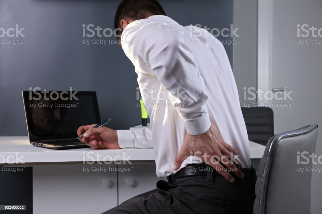 Business man suffering from back and neck pain in an office. Incorrect sitting posture problems, Muscle spasm, rheumatism. Pain relief, chiropractic concept. stock photo