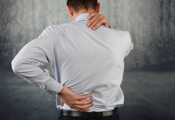 business man suffering from neck and back pain - schultersteife stock-fotos und bilder