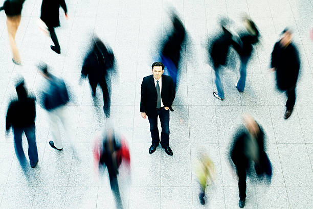 Business man surrounded by people stock photo