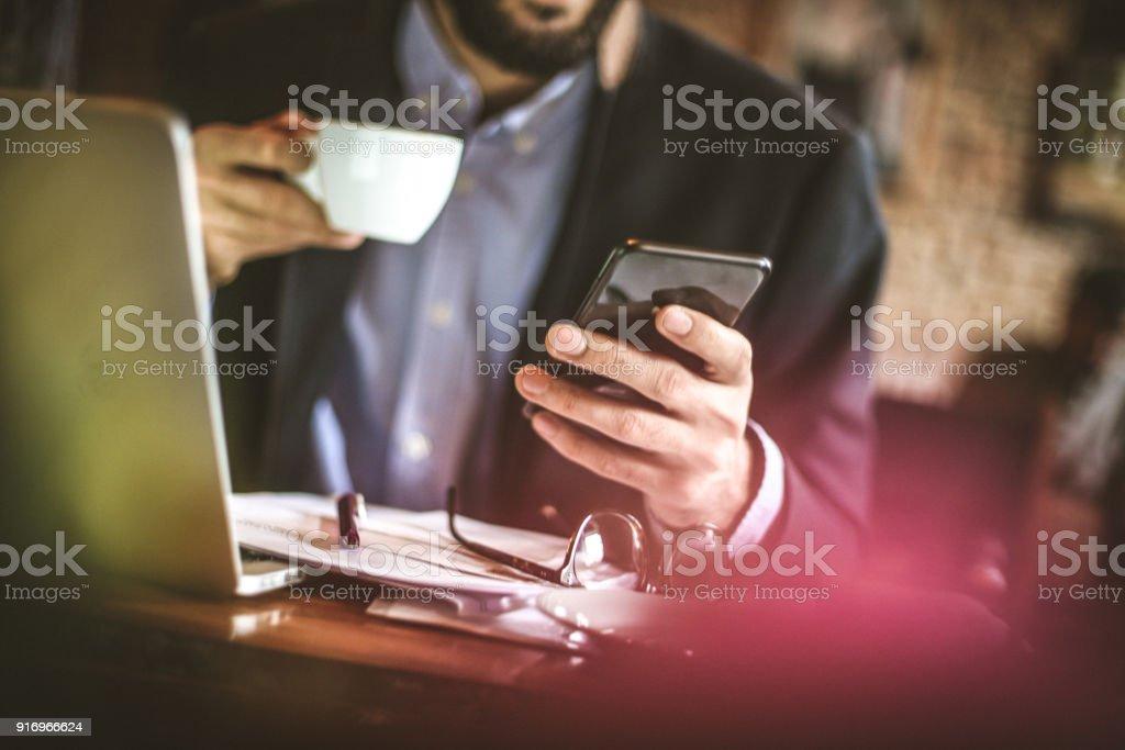 Business man take a break surfing online on smart phone.