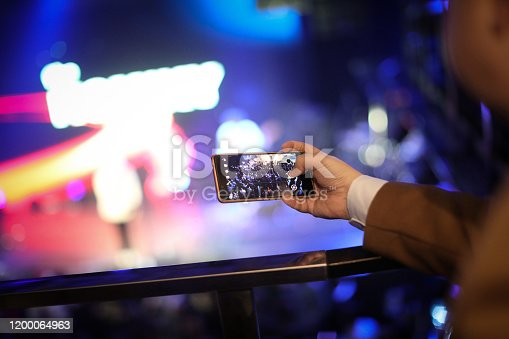 833314292 istock photo Business man taking photo with cell phone at a concert 1200064963