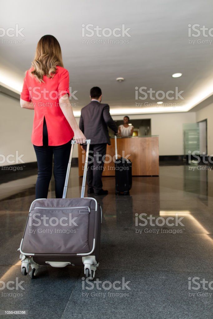 Business man talking to a latin receptionist in lobby stock photo