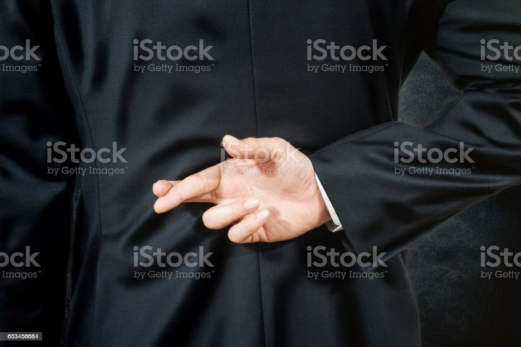 business man telling a lie, hold his finger crossed on his back stock photo