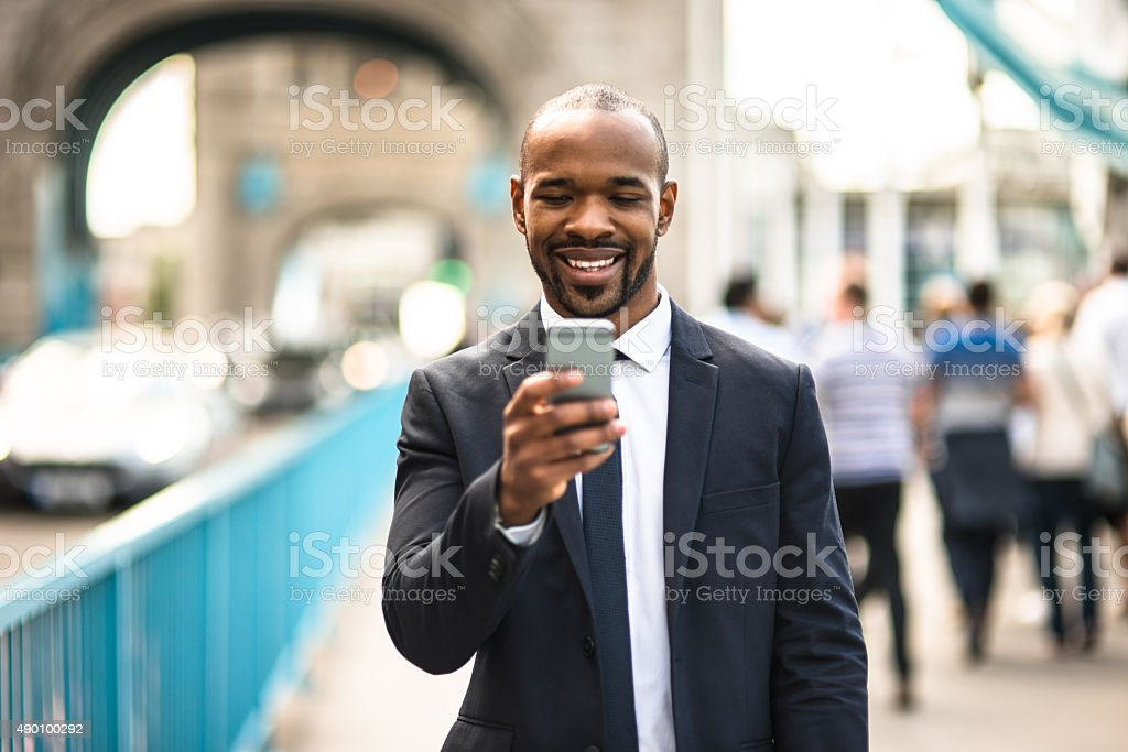 Business man text messaging at tower bridge in London stock photo