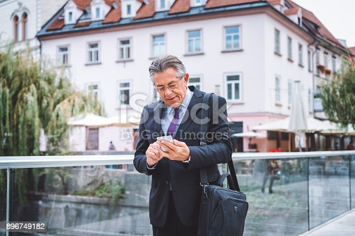 istock Business man texting on his phone 896749182