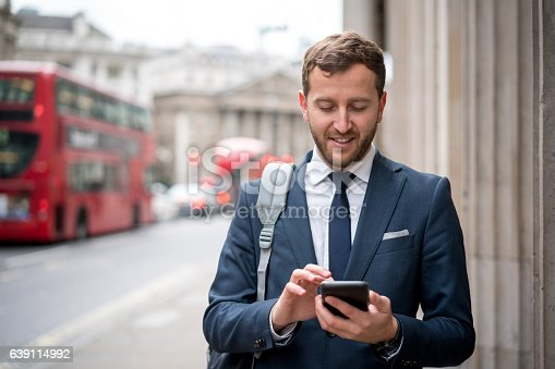 istock Business man texting on the street 639114992