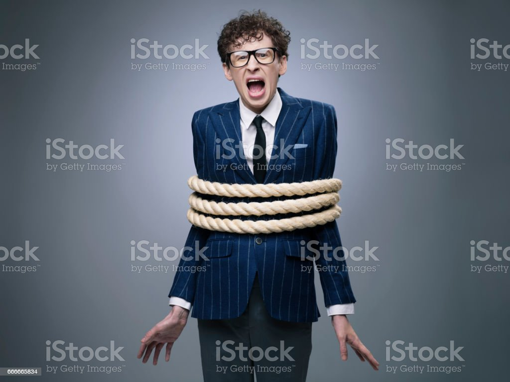 Business man tied up with rope stock photo