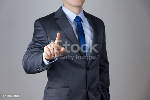 istock Business man touching an imaginary screen 471969499