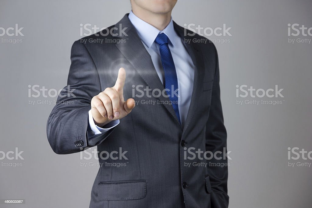 Business man touching an imaginary screen with lit finger stock photo