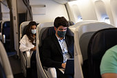 Business man traveling and wearing a facemask on the plane while using his laptop– COVID-19 pandemic lifestyle concepts