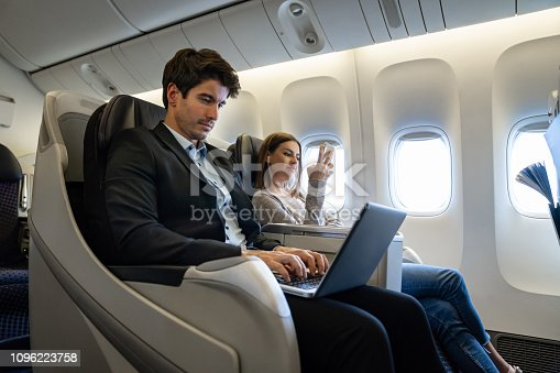 Portrait of a business man traveling by plane and working on his laptop computer - business trip concepts
