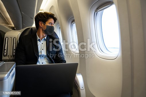 Business man traveling by plane wearing a facemask and using his laptop while looking through the window – COVID-19 pandemic