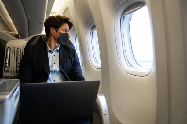 Business man traveling by plane wearing a facemask and using his laptop stock photo