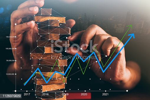 istock business man try to build wood block on wooden table and black background business organization startup concept 1125370020