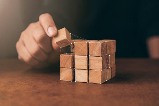 business-mann versuchen, bauen holz-block auf holztisch und unschärfe hintergrund geschäftskonzept organisation start - neue abenteuer stock-fotos und bilder