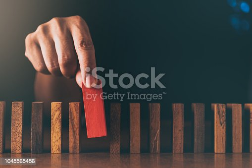 business man try to build wood block on wooden table and black bbusiness man try to choose red color wood block from others on wooden table and black background business organization startup conceptackground business organization startup concept