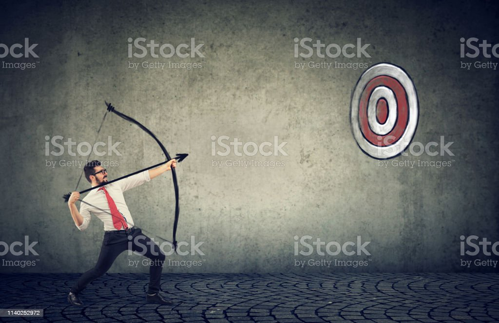 Determined business man trying to hit a target his goal with bow and...