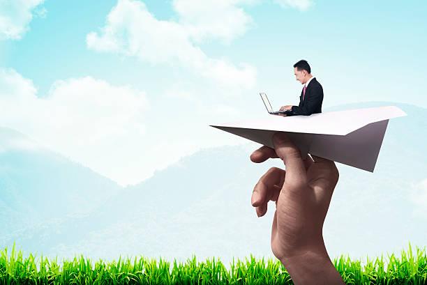 business-mann mit laptop schreiben auf dem papier flugzeug - origami mobil stock-fotos und bilder