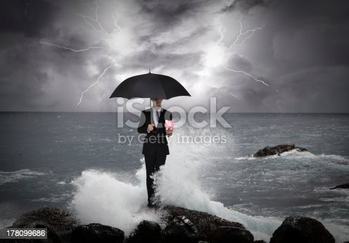 istock Business man under an umbrella in the sea 178099686