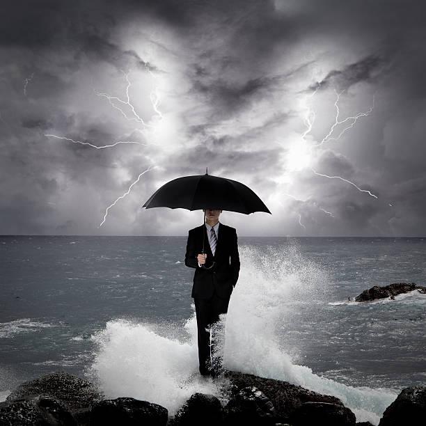 бизнес человек под зонтик на море - lightning стоковые фото и изображения