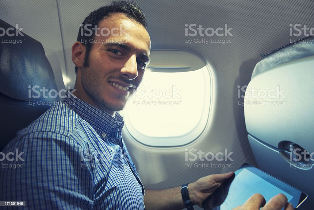 Business man using a digital tablet on the plane royalty-free stock photo