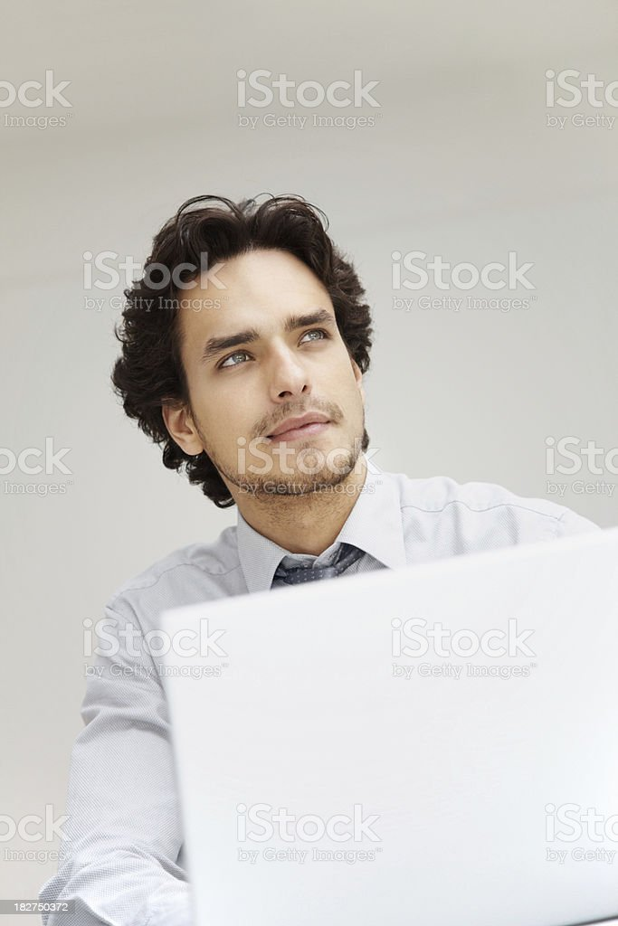 Business man using a laptop and looking away in thought royalty-free stock photo