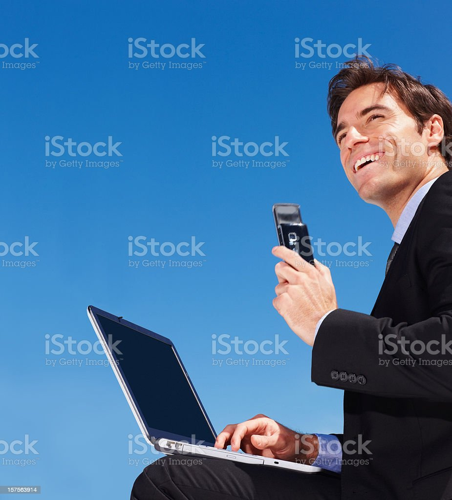Business man using a laptop while holding mobile phone royalty-free stock photo