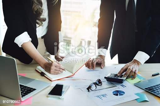 881542122istockphoto Business man using calculator and Businesswoman using notebook with stock crytocurrency document and laptop computer to analyze Trade shares. To profit from crytocurrency in 2018. 910790552