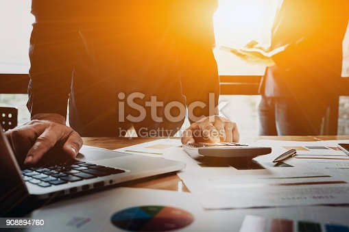 istock business man using calculator and laptop computer with partners 908894760
