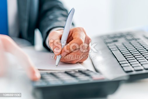 Photo of Male accountant calculations and analyzing data with calculator, Financing, Accounting, Doing finance, Economy, Savings Banking Concept. Close up, business man or lawyer accountant working on accounts using a calculator and writing on documents while sitting on his desk in modern office.