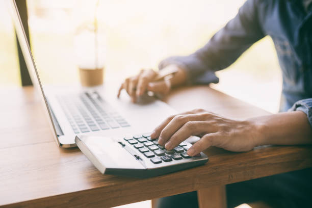 Business man  using calculator. Business man  using calculator,finance and economy concept through a laptop. expense stock pictures, royalty-free photos & images