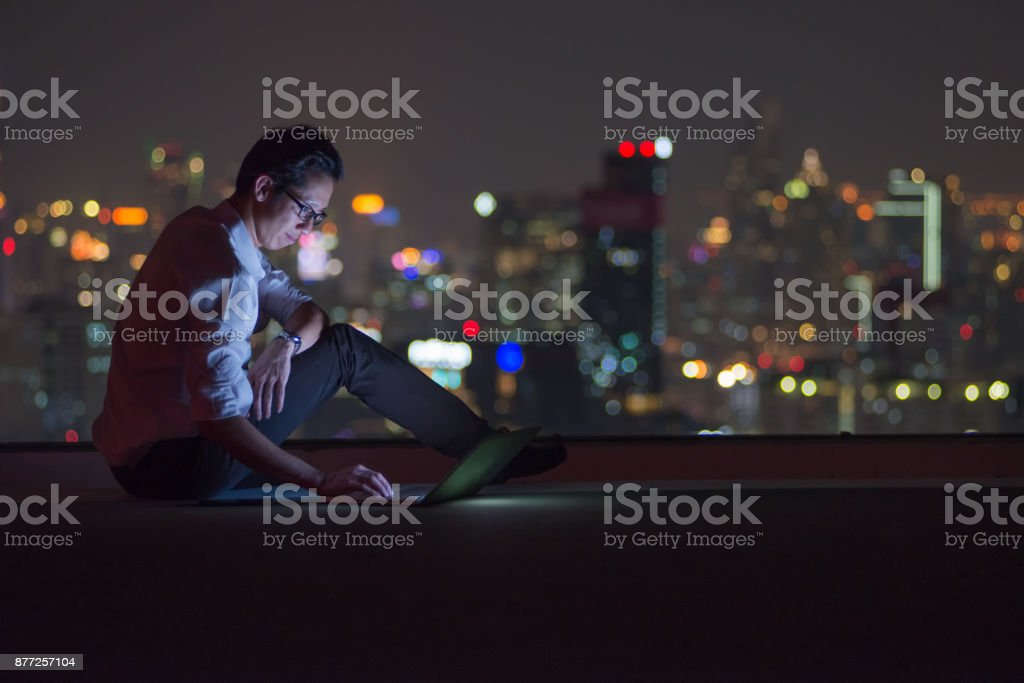 Business man using computer laptop on the rooftop of the city at night stock photo