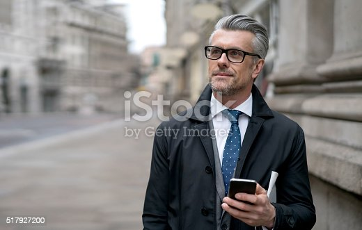 istock Business man using his cell phone on the street 517927200
