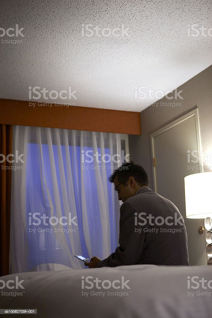 Business man using mobile phone sitting on bed in hotel room 免版稅 stock photo