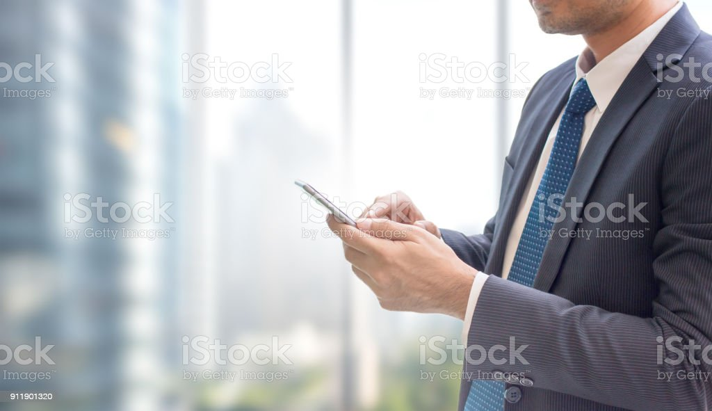 Business man using smart phone on window with city building background and copy space. stock photo