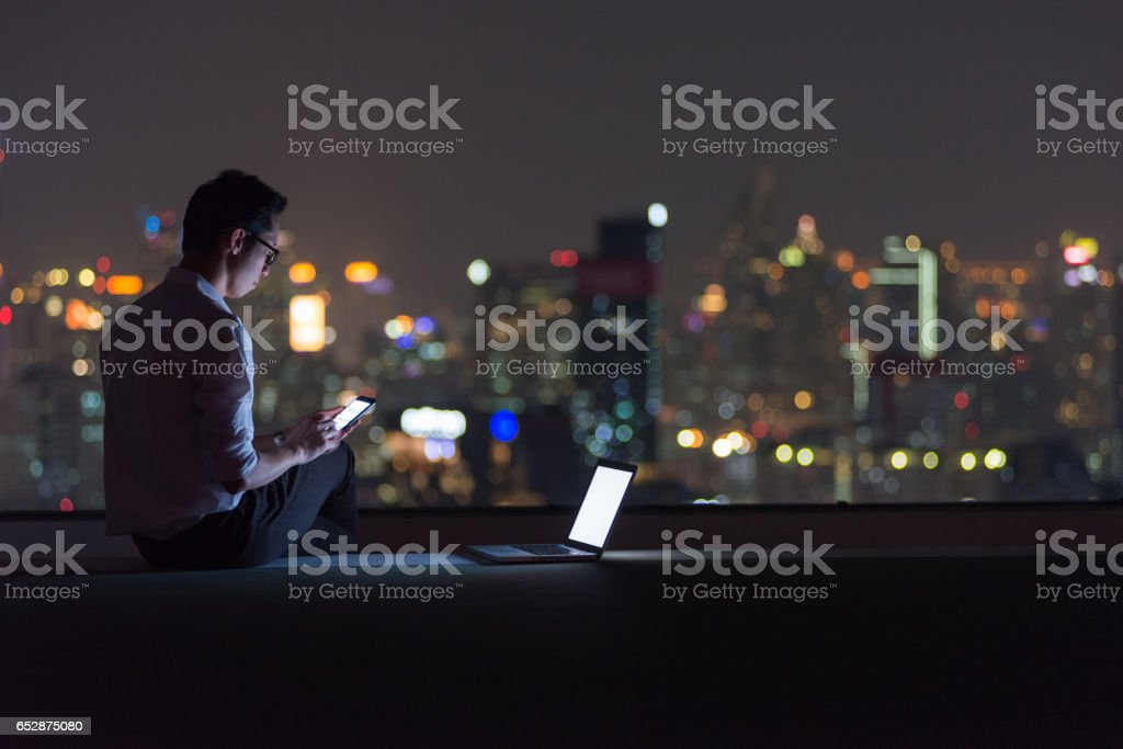 Business man using  smartphone and laptop on rooftop stock photo