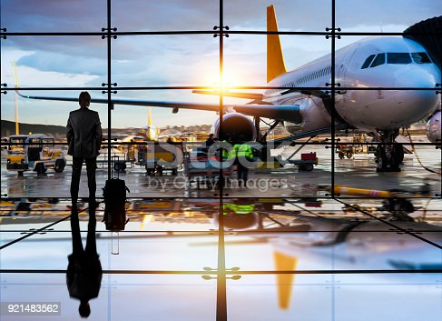 Passenger airplane getting ready for flight and business man waiting to board a flight in airport