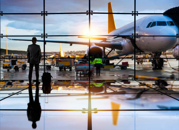 business man waiting to board a flight in airport - airport terminal stock photos and pictures