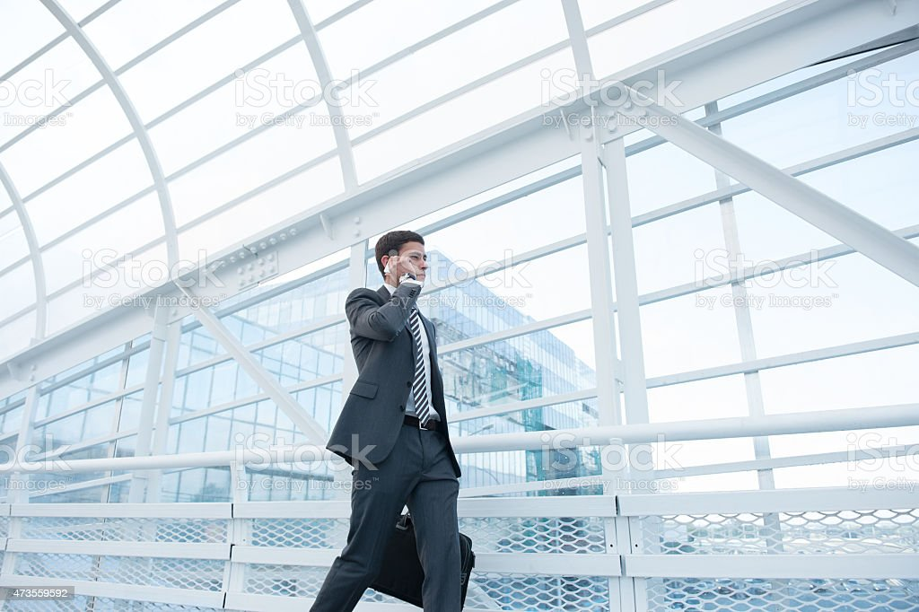 Business man walking down hallway talking on smartphone stock photo