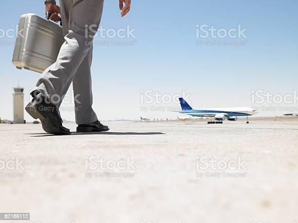 Hombre De Negocios Caminando Hacia Avión Foto de stock y más banco de imágenes de Maletín