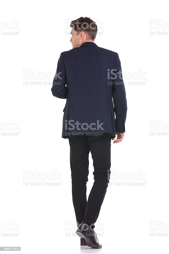 business man walking while looking to his side. stock photo