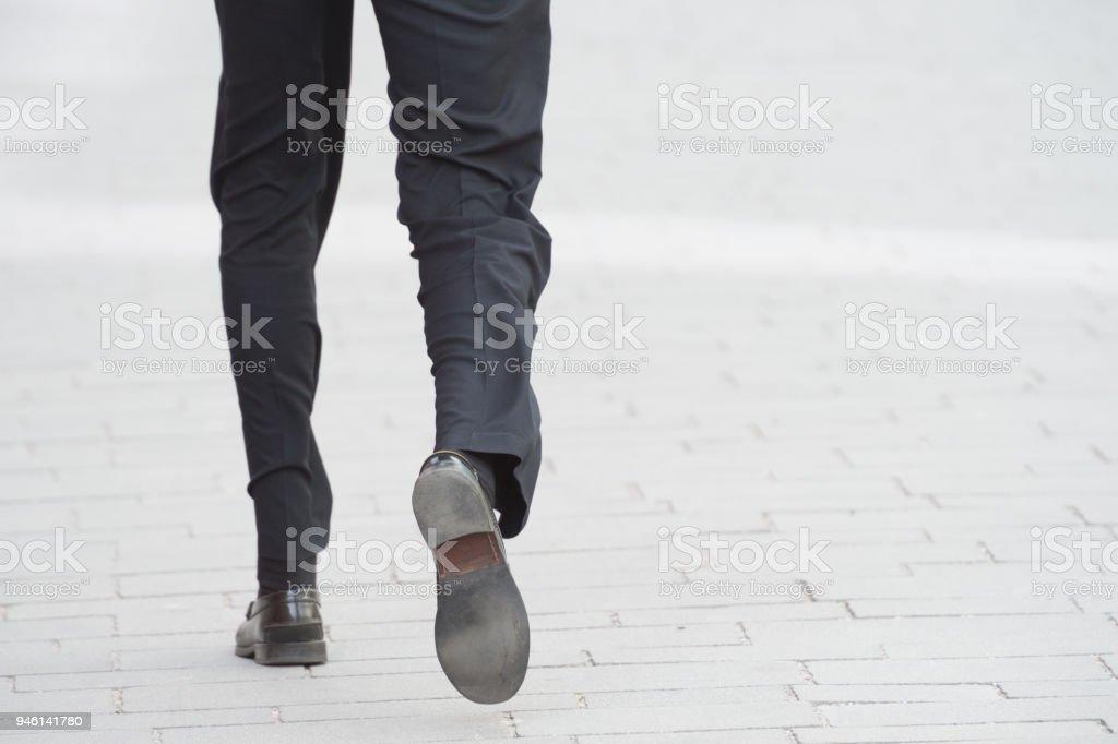 Business man wallking away on tiled street stock photo