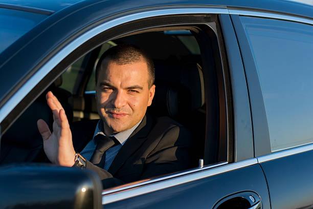homme d'affaires signe de la main - homme faire coucou voiture photos et images de collection