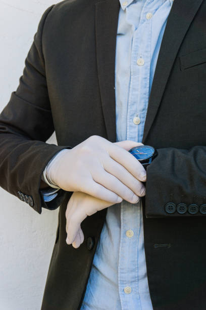 Business man wearing gloves looks the watch. Coronavirus : business man with gloves touches his watch. Body, hands and watch. Vertical capture. stock photo
