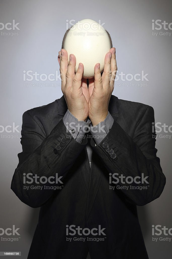 Business man with a blank face and ostrich egg stock photo