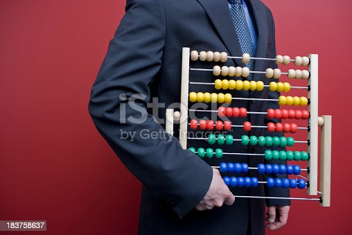 Humorous photo of a business man or accountant wearing a suit and tie holding an old fashioned vintage abacus for calculating numbers and doing accounting, finances, and taxes
