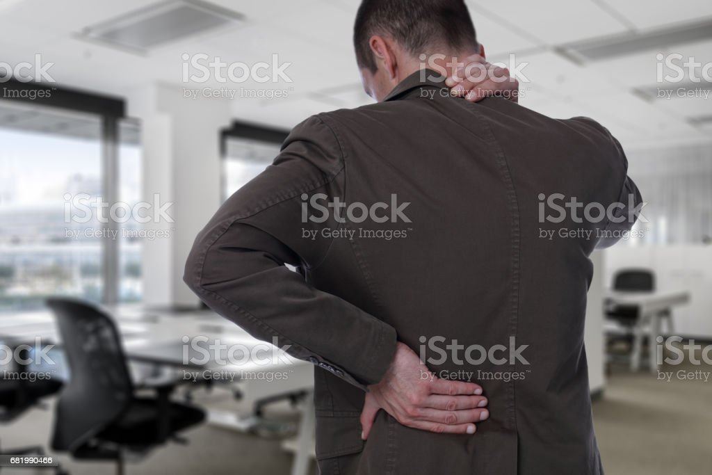 Business man with back pain in office . Pain relief concept stock photo